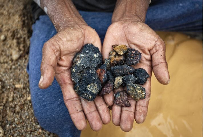 Miner shows rocks he found that contain tin. Source: friendsoftheearth.uk