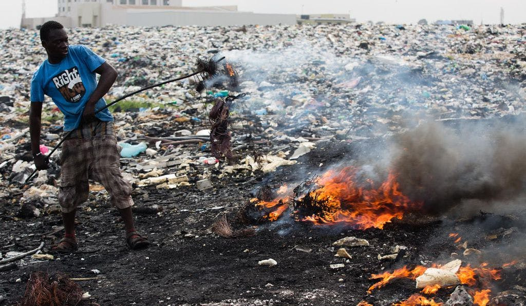 A worker in the 20-acre scrap yard in Agbogbloshie, Ghana burning insulated wire to recycle copper /©Jon Spaull